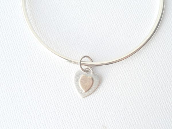 Small silver and gold charm on bangle